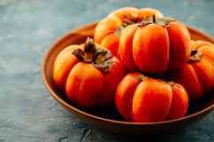 Fruta anaranjada madura del caqui en una placa de cerámica El caqui es una fuente de calcio, una fuente de potasio, carbohidratos fotos de archivo libres de regalías