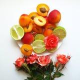 Fruta anaranjada y roja en una placa en un fondo blanco y un ramo colorido de flores al lado de él Alegre de summe foto de archivo libre de regalías