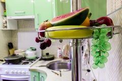 Fruta artificial en un estante del metal en la cocina imágenes de archivo libres de regalías