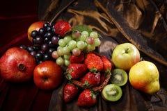 Fruta brillante jugosa, asperjada con agua, aún la vida de frutas estacionales y las bayas, visión superior Imagenes de archivo
