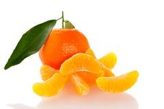 Fruta cítrica anaranjada sin pelar del mandarín con las hojas verdes y medio frescos Foto de archivo