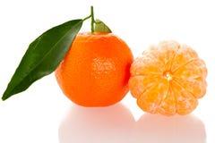 Fruta cítrica anaranjada sin pelar del mandarín con las hojas verdes y medio frescos Fotografía de archivo