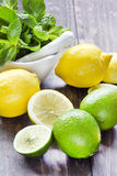 Fruta cítrica fresca en la tabla de madera rústica - cal, limón y menta Fotos de archivo libres de regalías