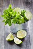 Fruta cítrica jugosa en la tabla de madera rústica - cal, limón y menta Fotografía de archivo