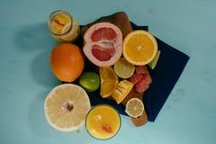 Fruta cítrica, naranjas, limones, cales, pomelo, pomelo en tablero del vintage, limonada y jugo en un vidrio foto de archivo libre de regalías