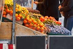 Fruta de compra de la gente de un vendedor ambulante foto de archivo