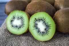 Fruta de kiwi, dos pedazos de kiwi con el cuchillo, kiwi que se coloca en piso de madera Imagenes de archivo