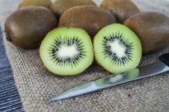 Fruta de kiwi, dos pedazos de kiwi con el cuchillo, kiwi que se coloca en piso de madera Imagen de archivo