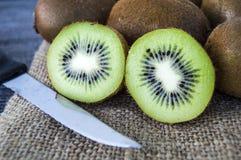 Fruta de kiwi, dos pedazos de kiwi con el cuchillo, kiwi que se coloca en piso de madera Fotos de archivo