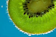 Fruta de kiwi en agua chispeante Fotos de archivo libres de regalías