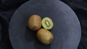 Fruta de kiwi giratoria en fondo negro Visi?n superior almacen de video