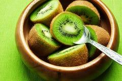 Fruta de kiwi madura jugosa en cuenco de madera con la cuchara Imagen de archivo