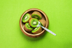 Fruta de kiwi madura jugosa en cuenco de madera en servilleta verde con la cuchara Foto de archivo libre de regalías