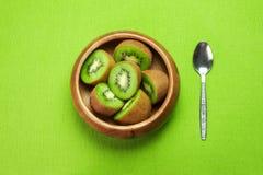 Fruta de kiwi madura jugosa en cuenco de madera en servilleta verde con la cuchara Fotografía de archivo