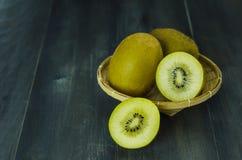 Fruta de kiwi y cortado con la cesta de bambú Imágenes de archivo libres de regalías