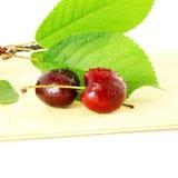 Fruta de la cereza con las hojas y los waterdrops en fondo blanco puro Fotografía de archivo libre de regalías