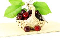 Fruta de la cereza con las hojas y los waterdrops en fondo blanco puro Fotografía de archivo