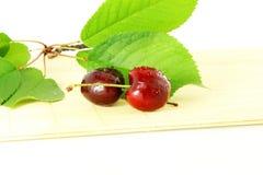 Fruta de la cereza con las hojas y los waterdrops en fondo blanco puro Foto de archivo libre de regalías
