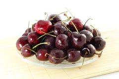 Fruta de la cereza con los waterdrops en fondo blanco puro Imagen de archivo