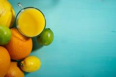 Fruta de la fruta cítrica, naranja, cal, limón, pomelo, pomelo con el zumo de naranja en un vidrio de vidrio Espacio para la firm Imagen de archivo libre de regalías