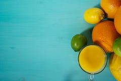 Fruta de la fruta cítrica, naranja, cal, limón, pomelo, pomelo con el zumo de naranja en un vidrio de vidrio Espacio para la firm Imagen de archivo