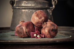 Fruta de la granada en la bandeja oxidada y una flor Foto de archivo