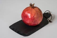 Fruta de la granada roja madura en una tabla de cortar negra fotos de archivo