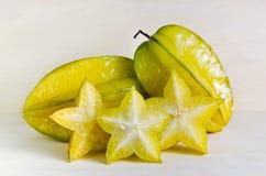 Fruta de la manzana de estrella con el medio corte transversal aislado en verraco de madera Fotos de archivo