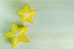 Fruta de la manzana de estrella con el medio corte transversal aislado en verraco de madera Foto de archivo