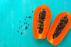 Fruta de la papaya en fondo de madera Rebanadas de papaya dulce en fondo de madera, papayas partidas en dos con las hojas, Foto de archivo