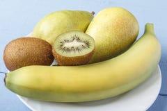 Fruta de las peras, del plátano y de kiwi en el primer de madera del fondo Desayuno o cena dietético con las frutas maduras natur Imagen de archivo