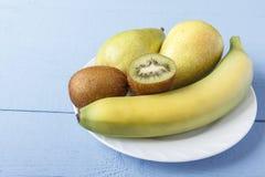 Fruta de las peras, del plátano y de kiwi en la placa blanca Desayuno o cena sano con las frutas maduras naturales en la tabla de Fotografía de archivo libre de regalías