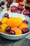 Fruta de piedra del otoño en la tabla de madera, los melocotones amarillos y las cerezas, visión superior Foto de archivo