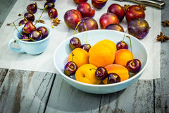 Fruta de piedra del otoño en la tabla de madera, los melocotones amarillos y las cerezas, visión superior Imagen de archivo