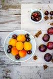Fruta de piedra del otoño en la tabla de madera, los melocotones amarillos y las cerezas, visión superior Imagen de archivo libre de regalías