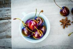 Fruta de piedra en la tabla de madera, cerezas maduras, visión plana del otoño Foto de archivo