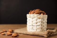 Fruta del bocado de la almendra en la cesta blanca en de madera Imagenes de archivo