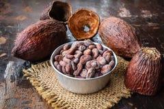 Fruta del cacao y granos de cacao secados en un cuenco en la tabla imagen de archivo
