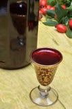 Fruta del escaramujo y licor del alcohólico en una botella y un vidrio Imagen de archivo libre de regalías