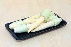 Fruta del maíz de bebé agrupada en la placa negra en el tablero de madera Fotos de archivo libres de regalías