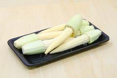 Fruta del maíz de bebé agrupada en la placa negra en el tablero de madera Fotografía de archivo libre de regalías