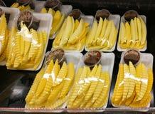 Fruta del mango de la rebanada en bandeja plástica en venta en mercado imagenes de archivo