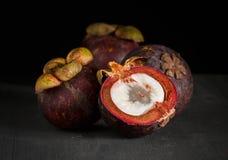 Fruta del mangostán, mitad, entera en fondo de madera oscuro imagenes de archivo
