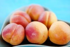 Fruta deliciosa de los melocotones en una placa en forma de corazón en un fondo de madera azul Fotos de archivo