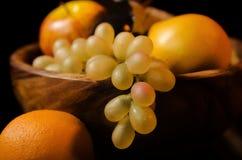 Fruta en un plato de madera Fotos de archivo