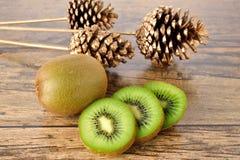 Fruta entera y cortada del primer de kiwi en la tabla de madera Foto de archivo