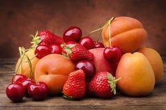 Fruta estacional con las frutas rojas y anaranjadas Fotografía de archivo