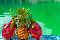 Fruta exótica contra la perspectiva de la piscina en un día soleado imagen de archivo
