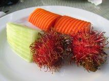 Fruta exótica en una placa Rambutan, papaya fotografía de archivo