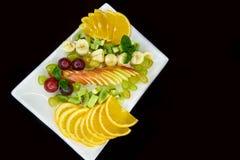 Fruta fresca cortada en una placa blanca Fotografía de archivo